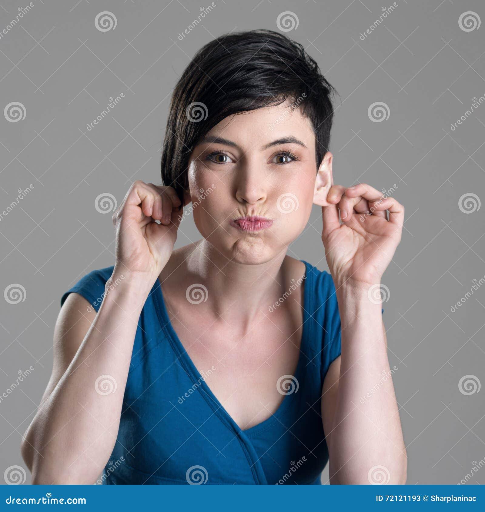 Jeune femme puérile espiègle mignonne de cheveux courts faisant la grimace regardant l appareil-photo