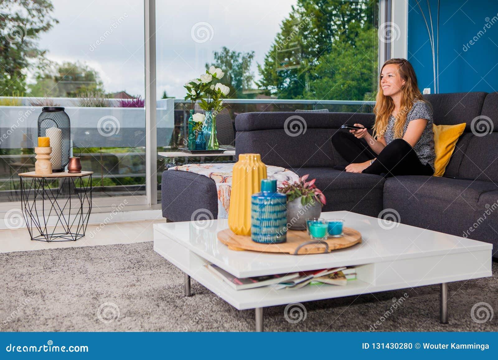 Jeune femme refroidissant et regardant la TV du divan