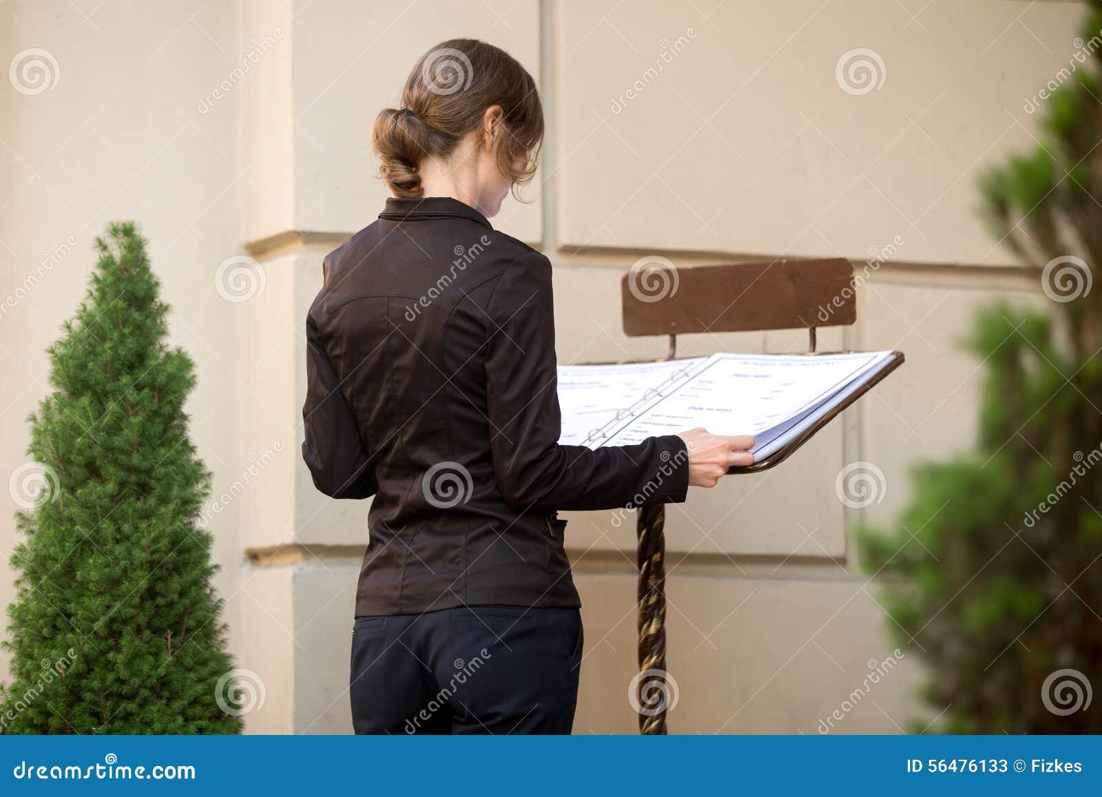 Jeune femme regardant le menu de restaurant sur la rue