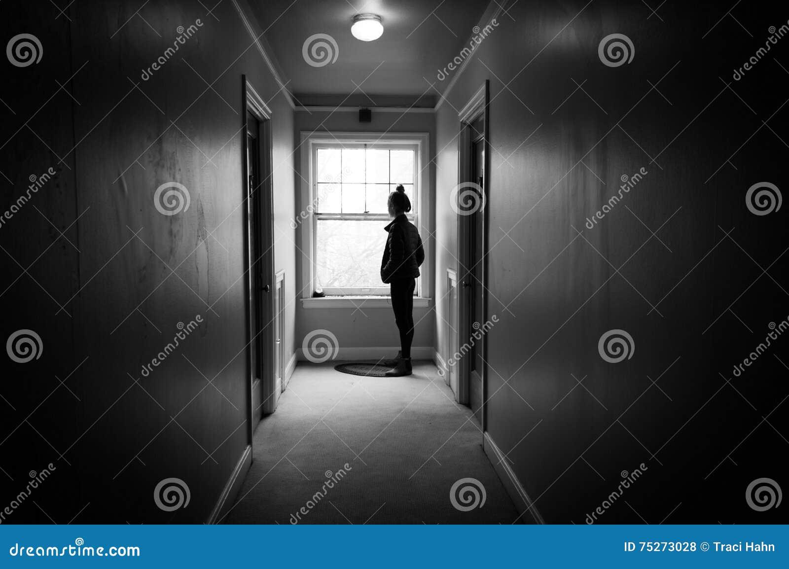 Jeune femme regardant une fenêtre dans un couloir sombre