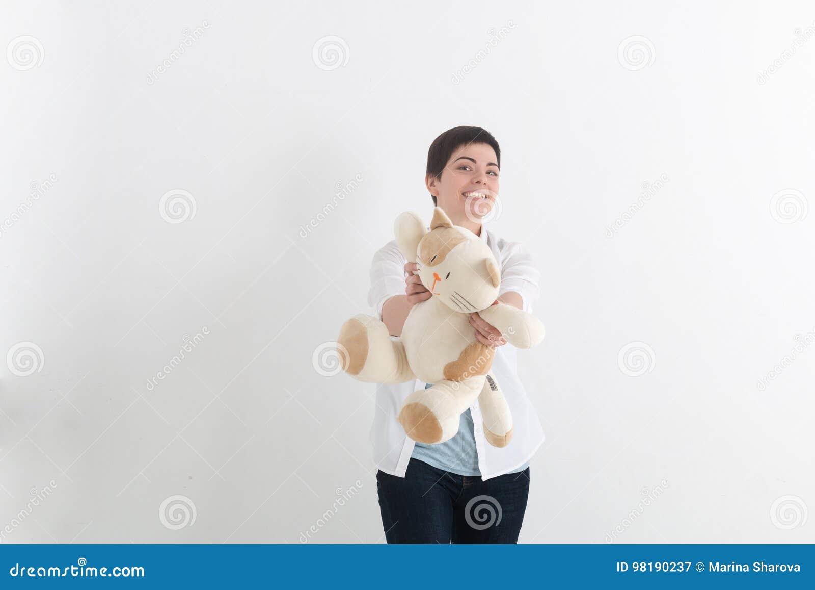 Jeune femme riante avec les cheveux courts dans le style occasionnel donnant le chat en avant de jouet de peluche et regardant l