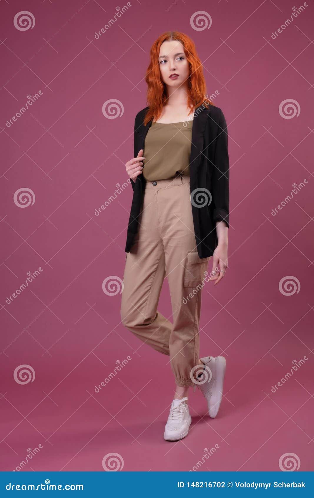 Jeune femme rousse attirante regardant la caméra