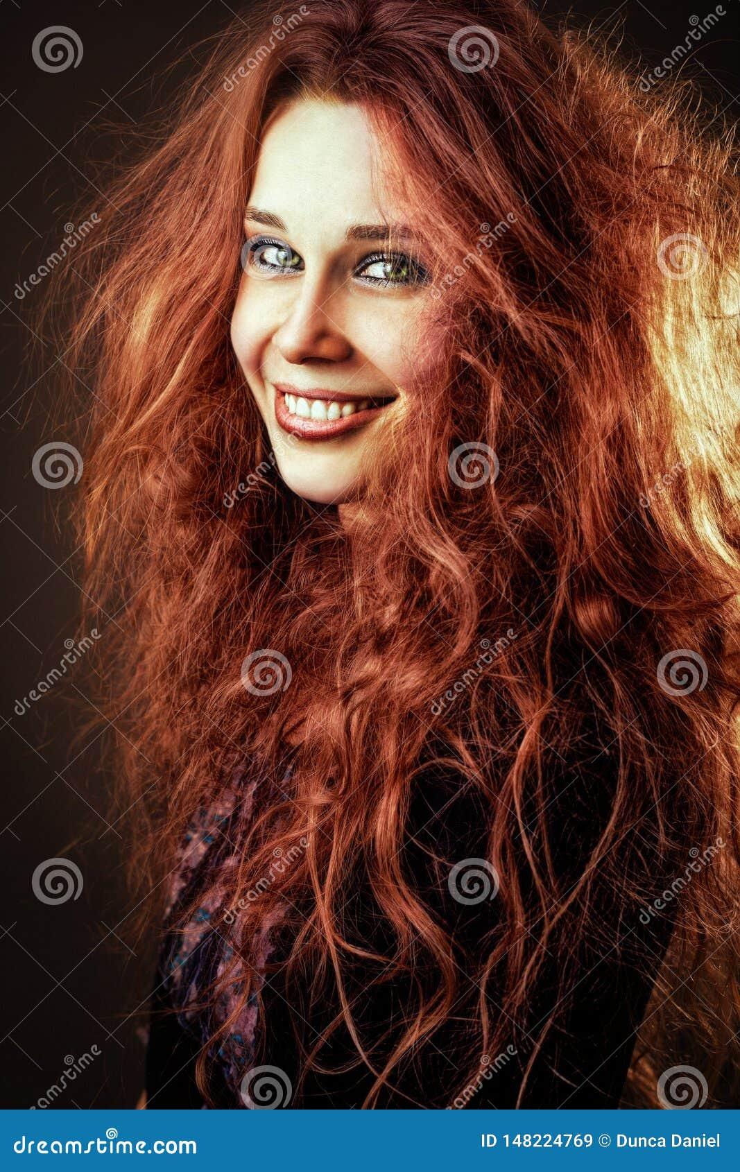 Jeune femme rousse de sourire heureuse avec de longs cheveux bouclés