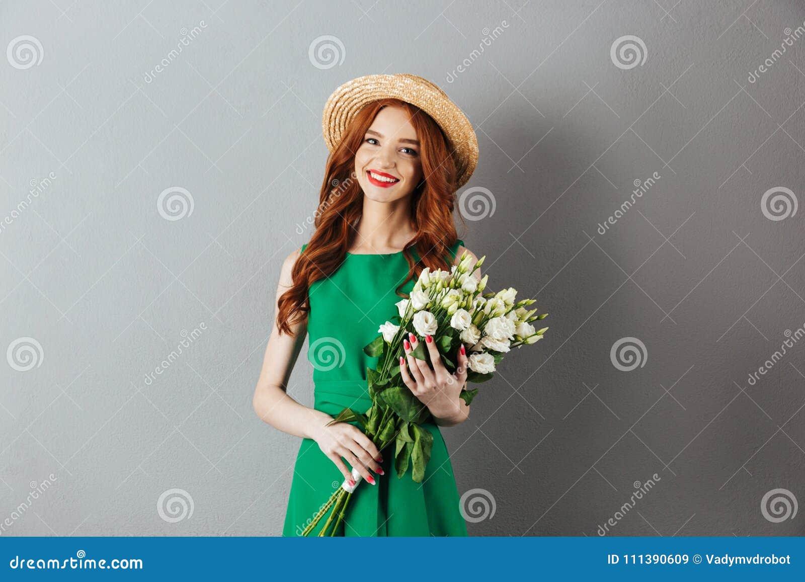 Jeune femme rousse gaie tenant des fleurs