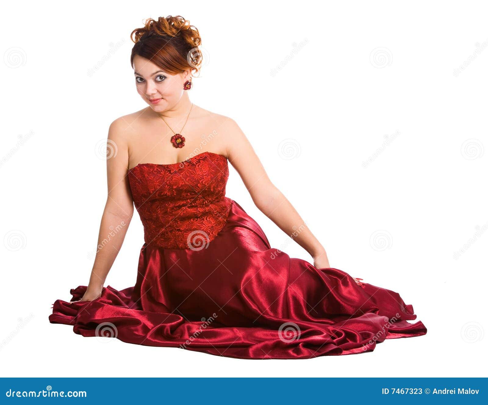 Jeune femme s asseyant dans la robe rouge.