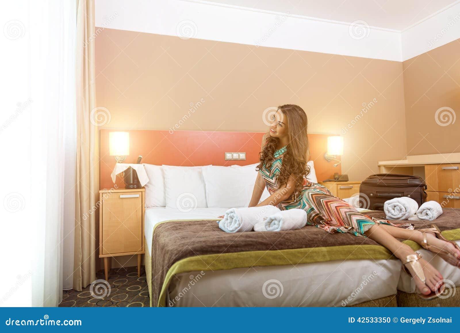 Jeune femme s 39 asseyant dans le lit d 39 une chambre d 39 h tel for Chambre 13 dans les hotels