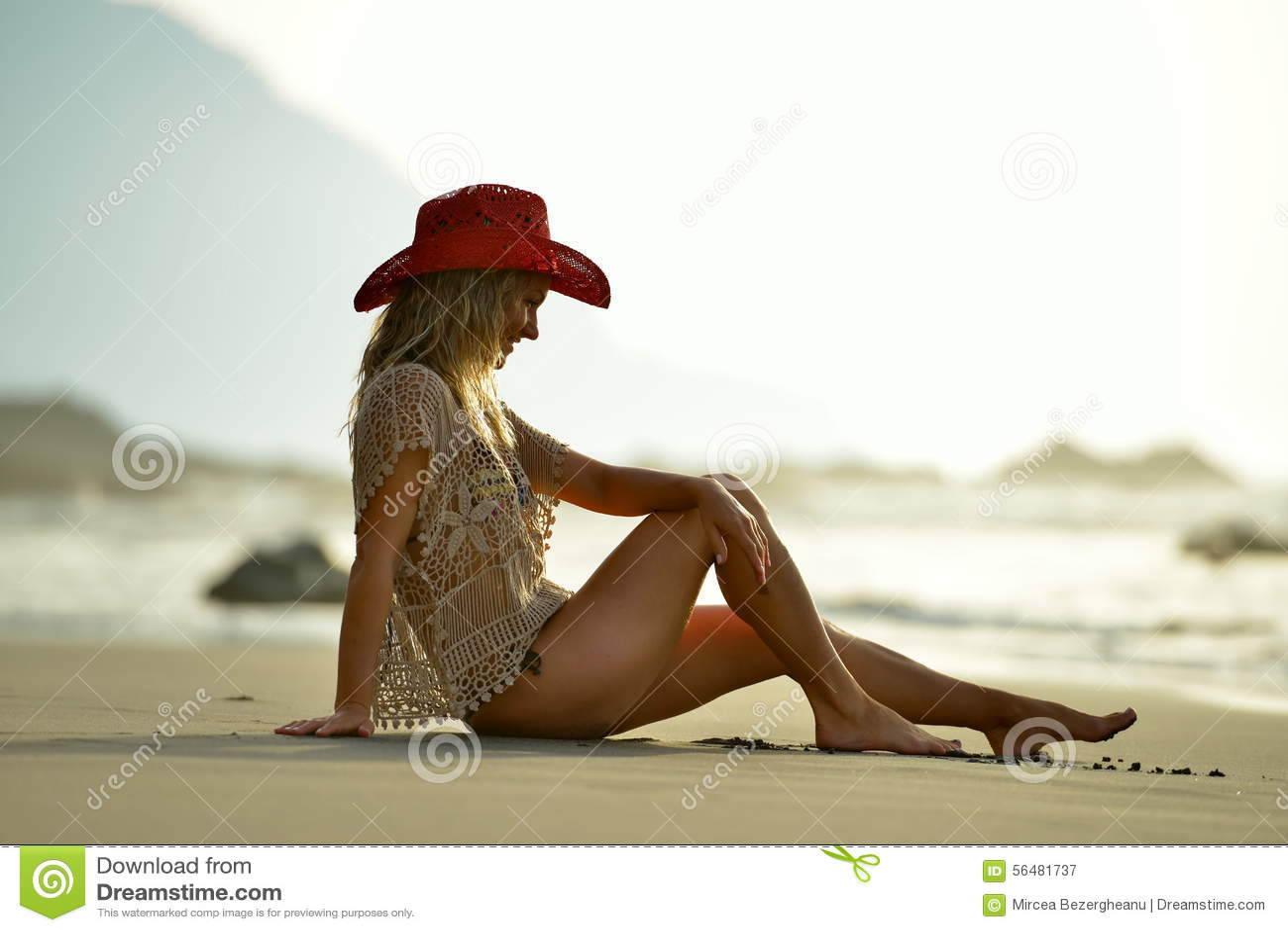 Jeune femme s asseyant sur la plage
