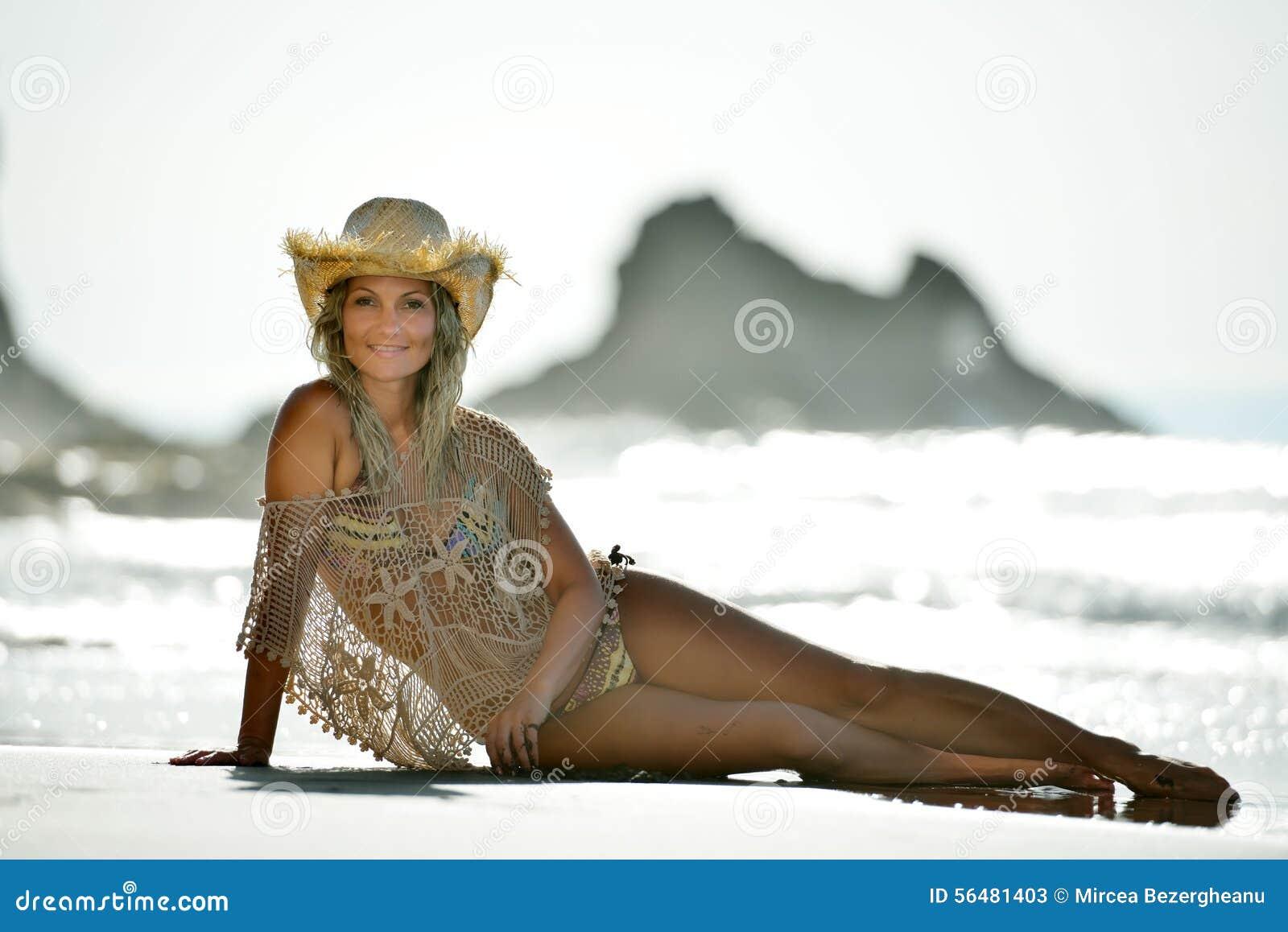 Jeune femme s asseyant sur la plage dans des vacances d été
