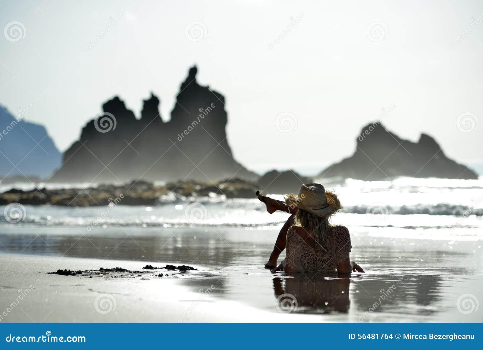 Jeune femme s asseyant sur la plage en été