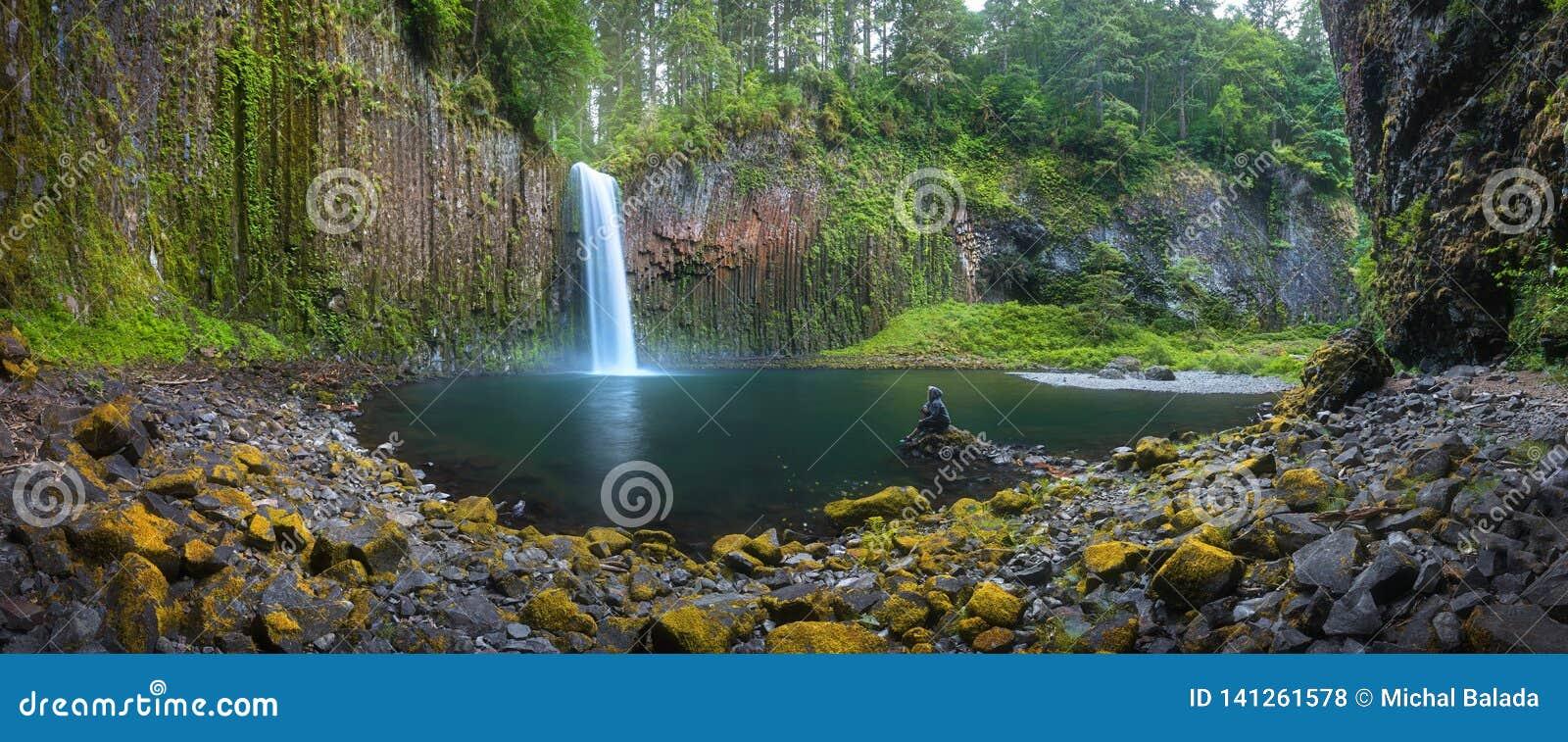 Jeune femme s asseyant sur la roche ? la belle cascade de la crique d Abiqua, automnes d Abiqua, Or?gon, Etats-Unis