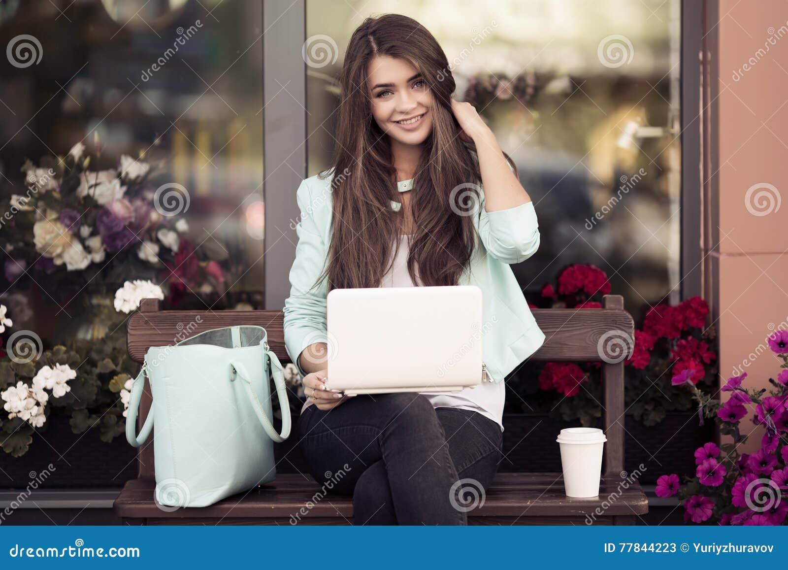 Jeune femme s asseyant sur le banc et à l aide de l ordinateur portable