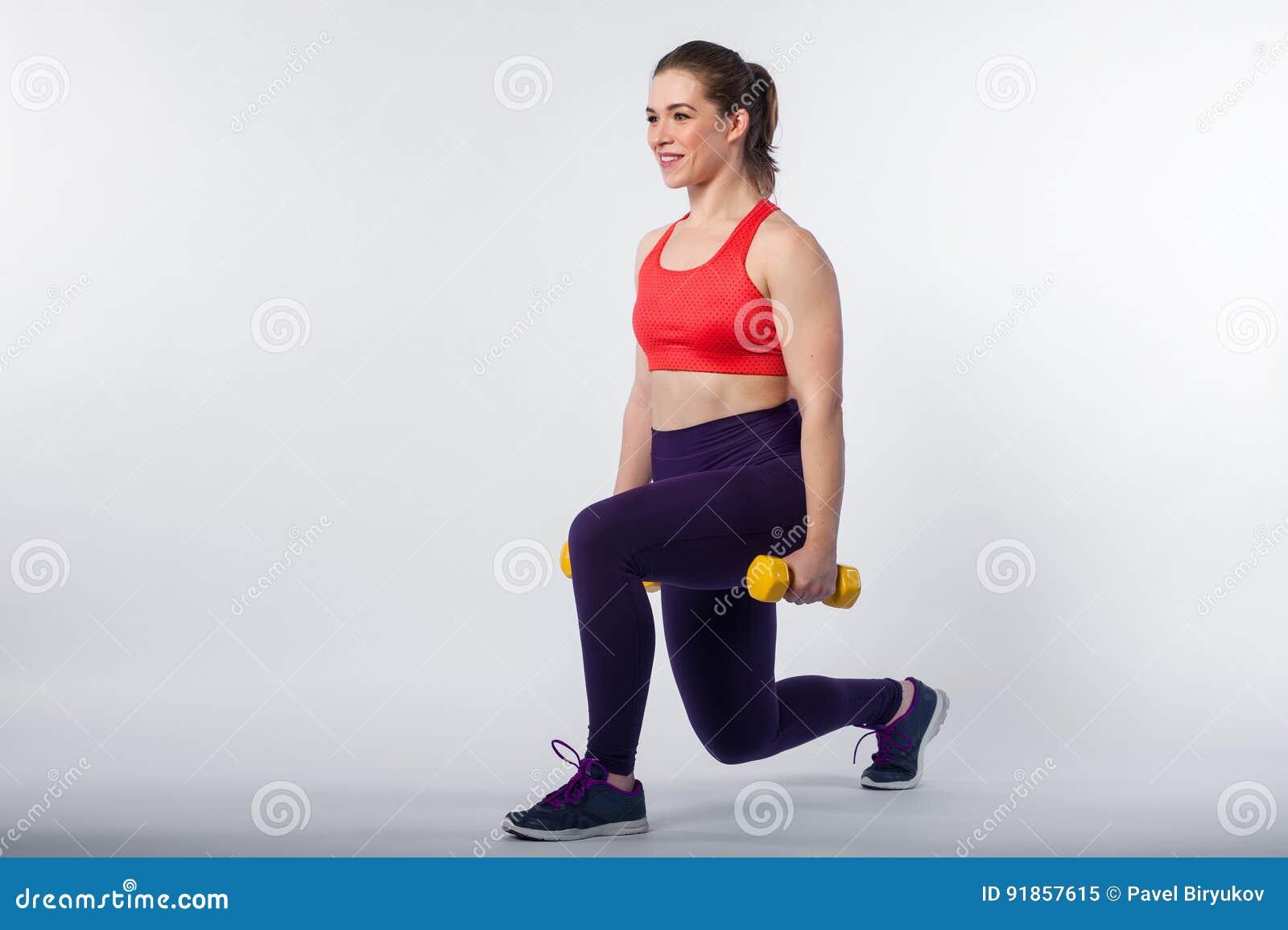 Jeune femme s exerçant avec des poids dans le studio