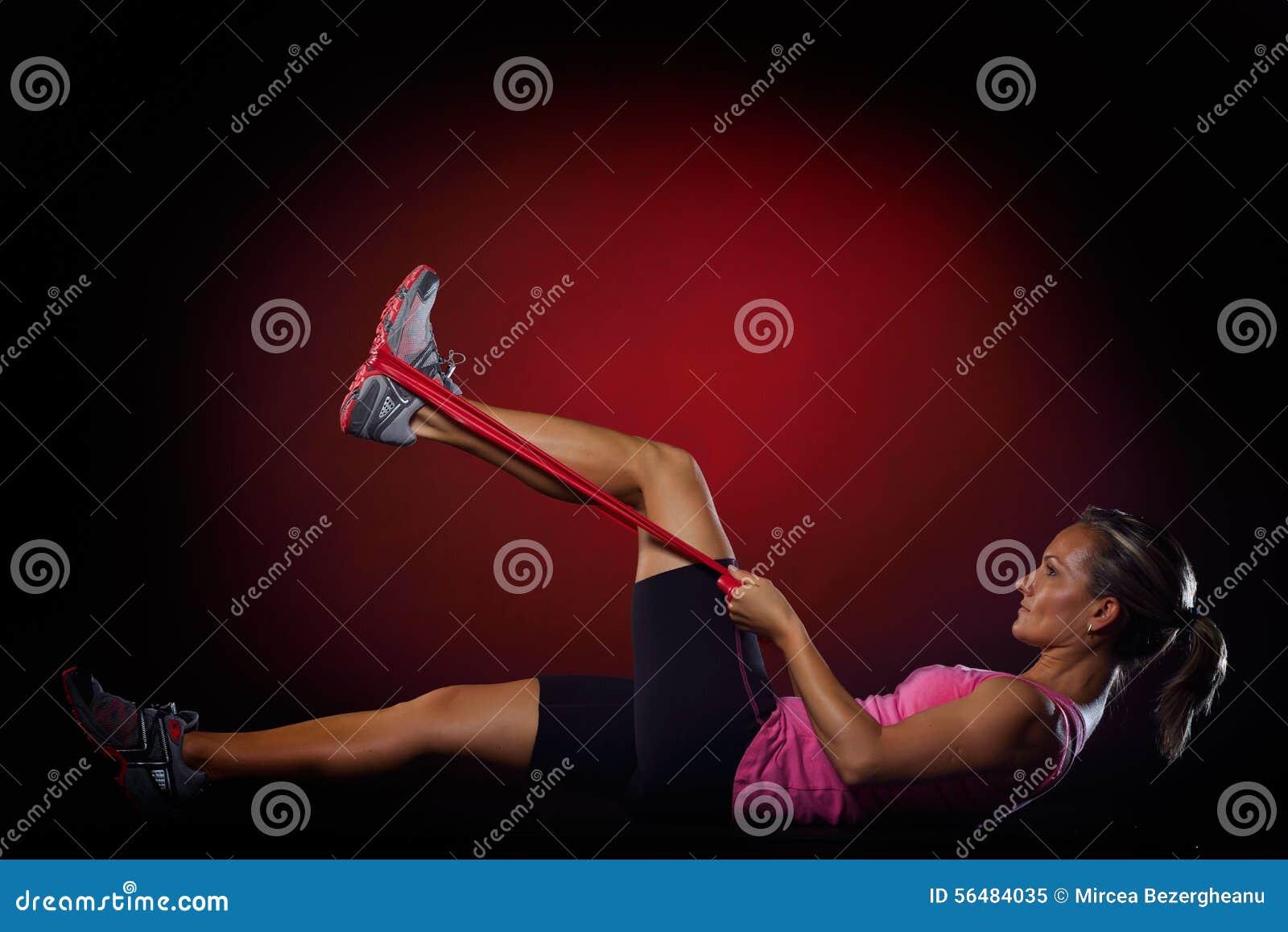 Jeune femme s exerçant avec la bande élastique de forme physique