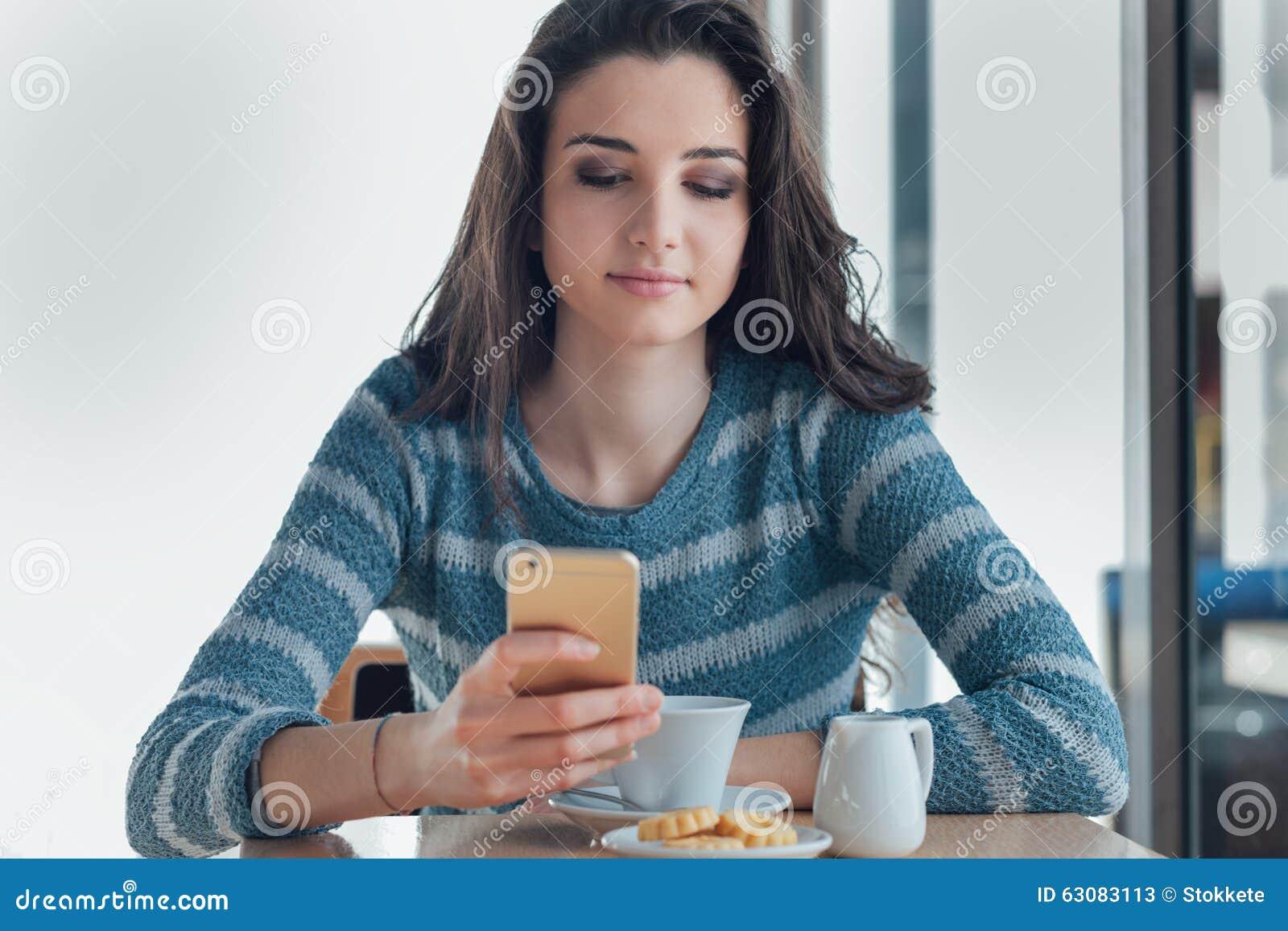 Download Jeune Femme Sûre Au Café Utilisant Un Smartphone Image stock - Image du insousiant, fille: 63083113