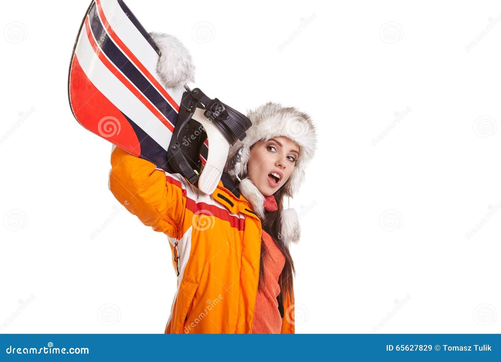 Jeune femme se tenant avec le surf des neiges d isolement sur le blanc