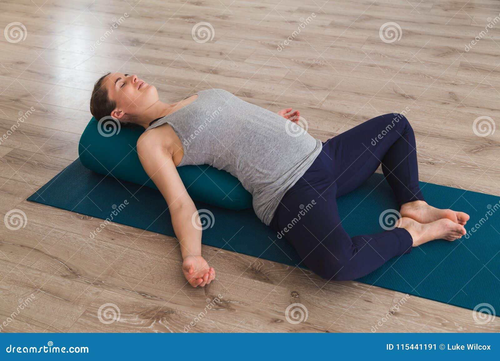 Jeune femme se trouvant sur le tapis de yoga utilisant le coussin de traversin