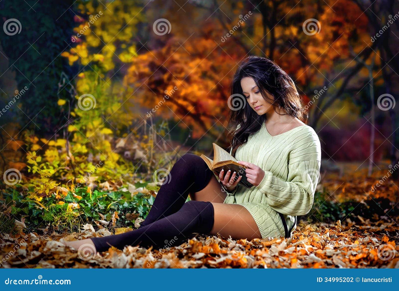 Jeune femme sensuelle caucasienne lisant un livre dans un paysage romantique d automne. Portrait de fille assez jeune dans la forê