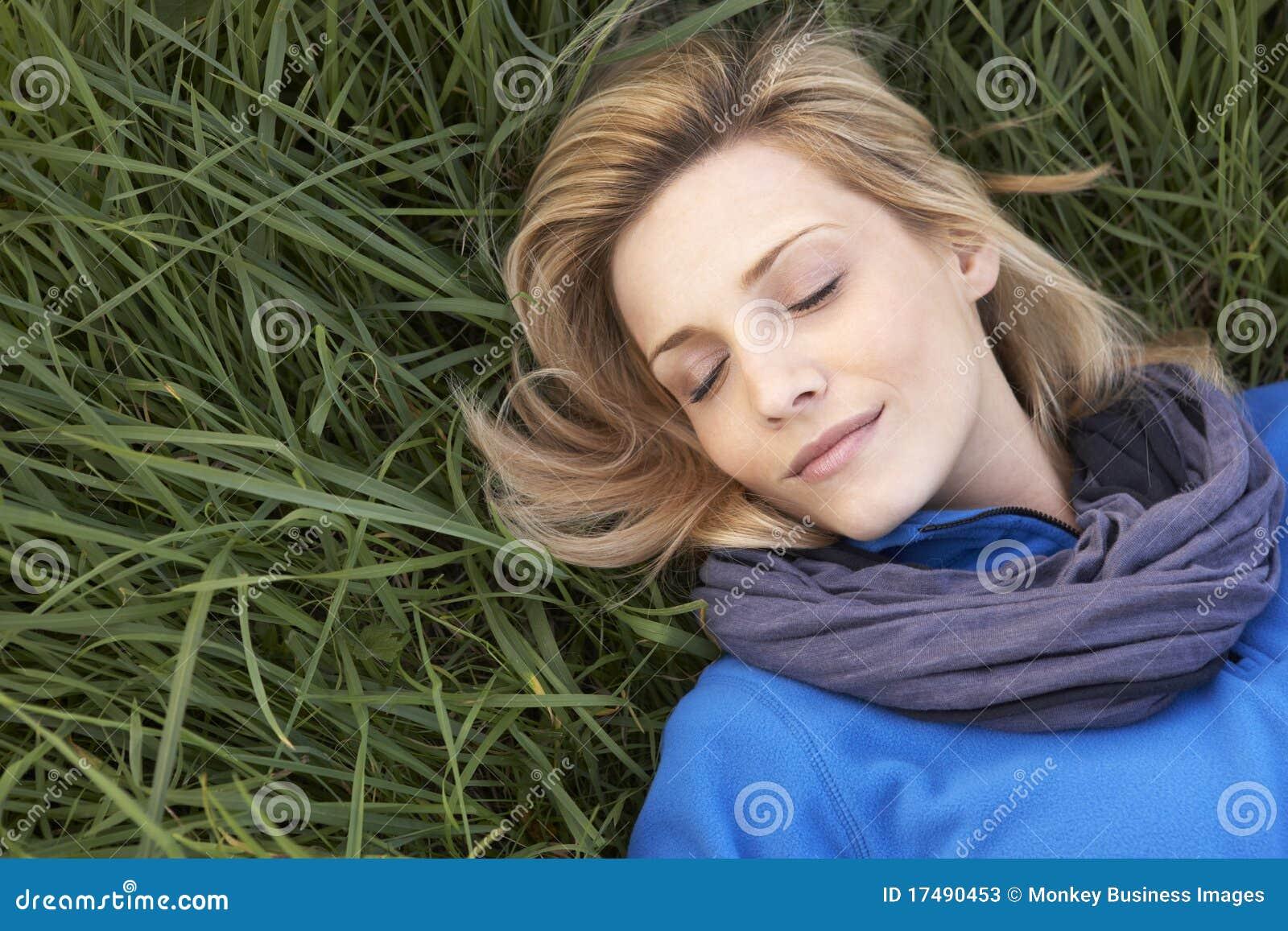 Jeune femme seul faisant une sieste sur l herbe