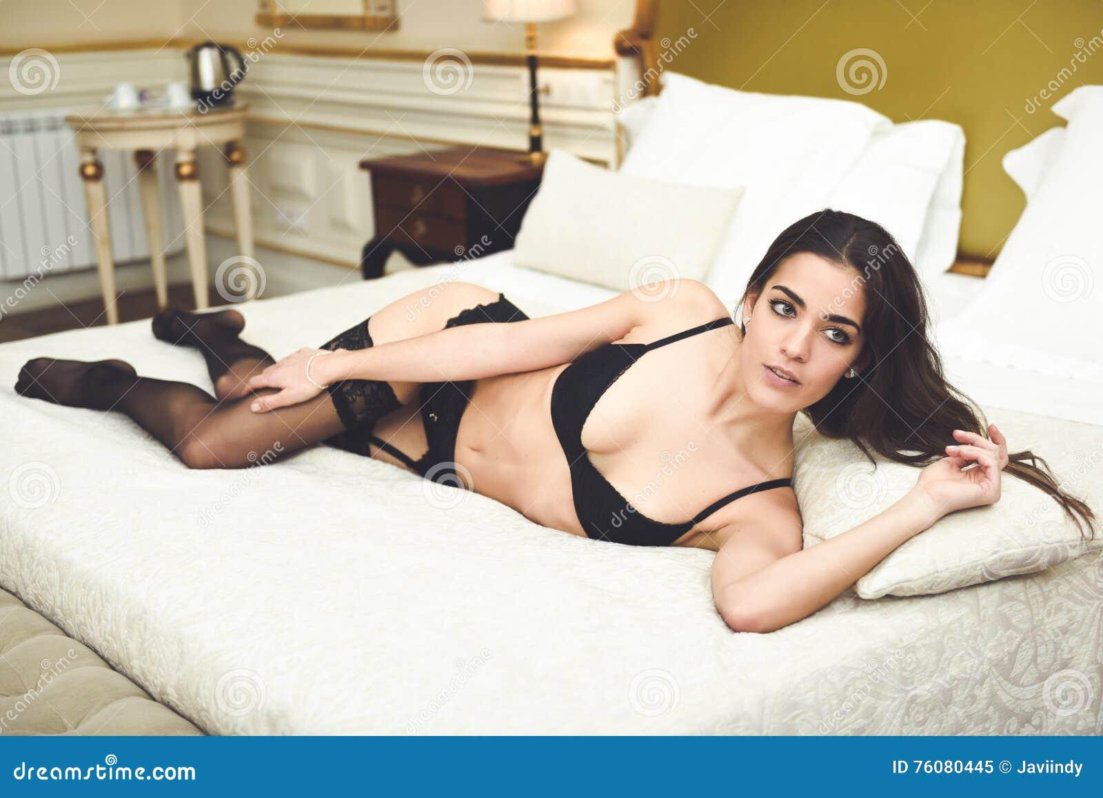 Jeune femme sexy dans la lingerie posant sur le lit