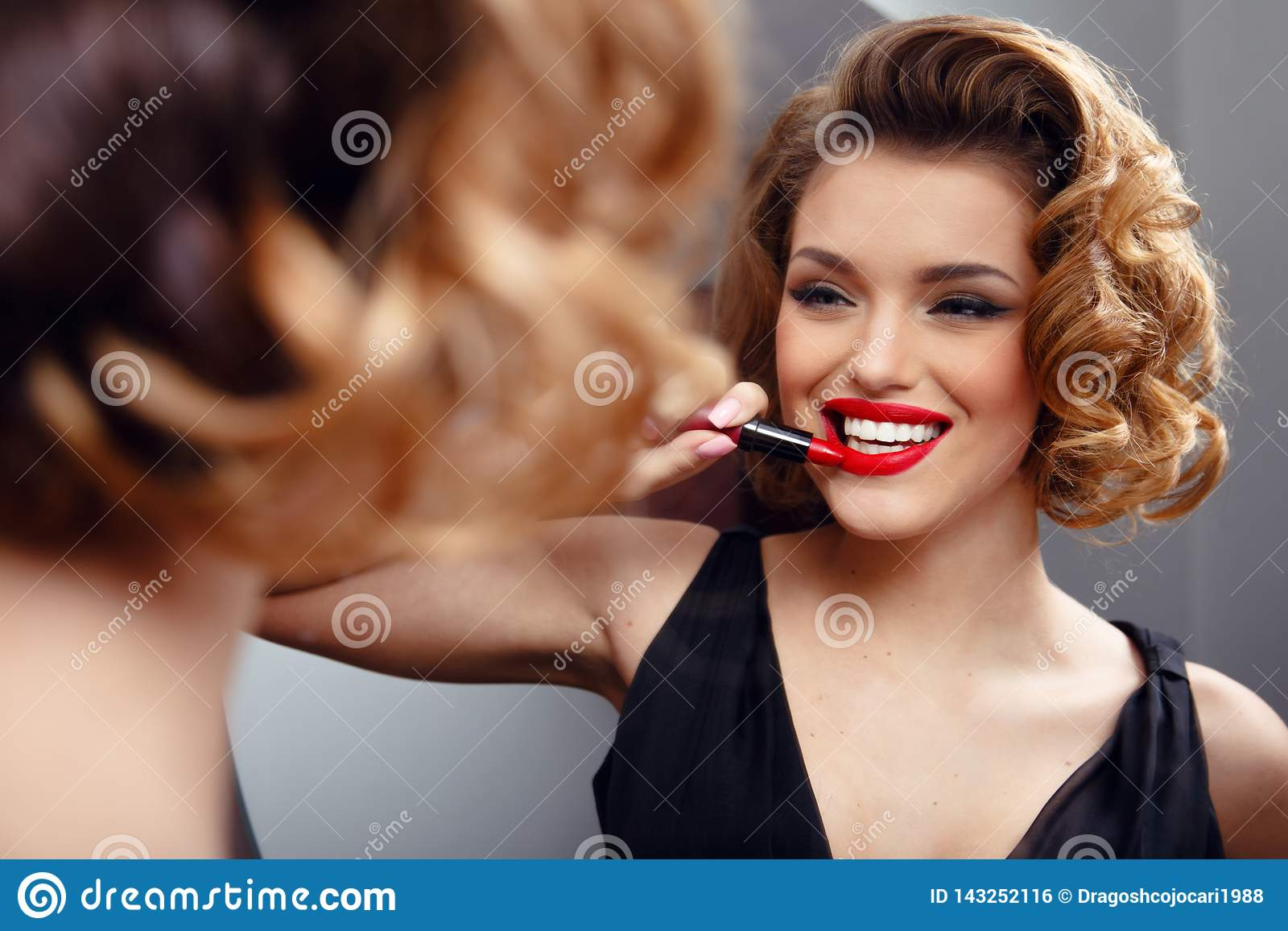 Jeune femme sexy séduisante appliquant le rouge à lèvres rouge sur les lèvres, regardant dans un miroir Rétro concept Employez le