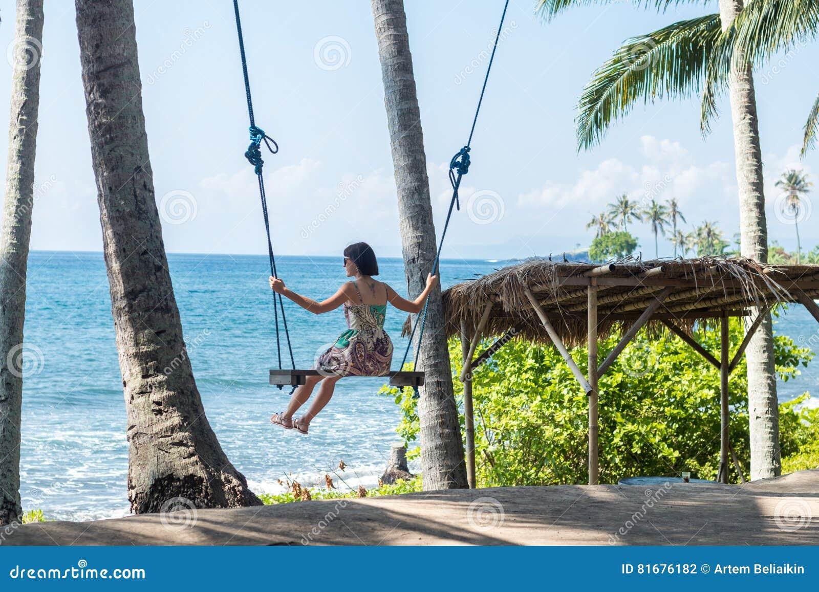 Jeune femme sexy s asseyant sur l oscillation sur la plage tropicale, île Bali, Indonésie de paradis Jour ensoleillé, vacances he