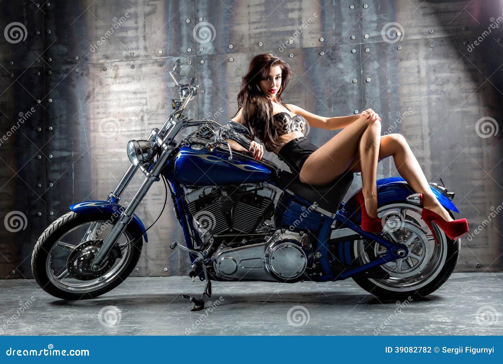 Jeune femme sexy s asseyant sur la moto.