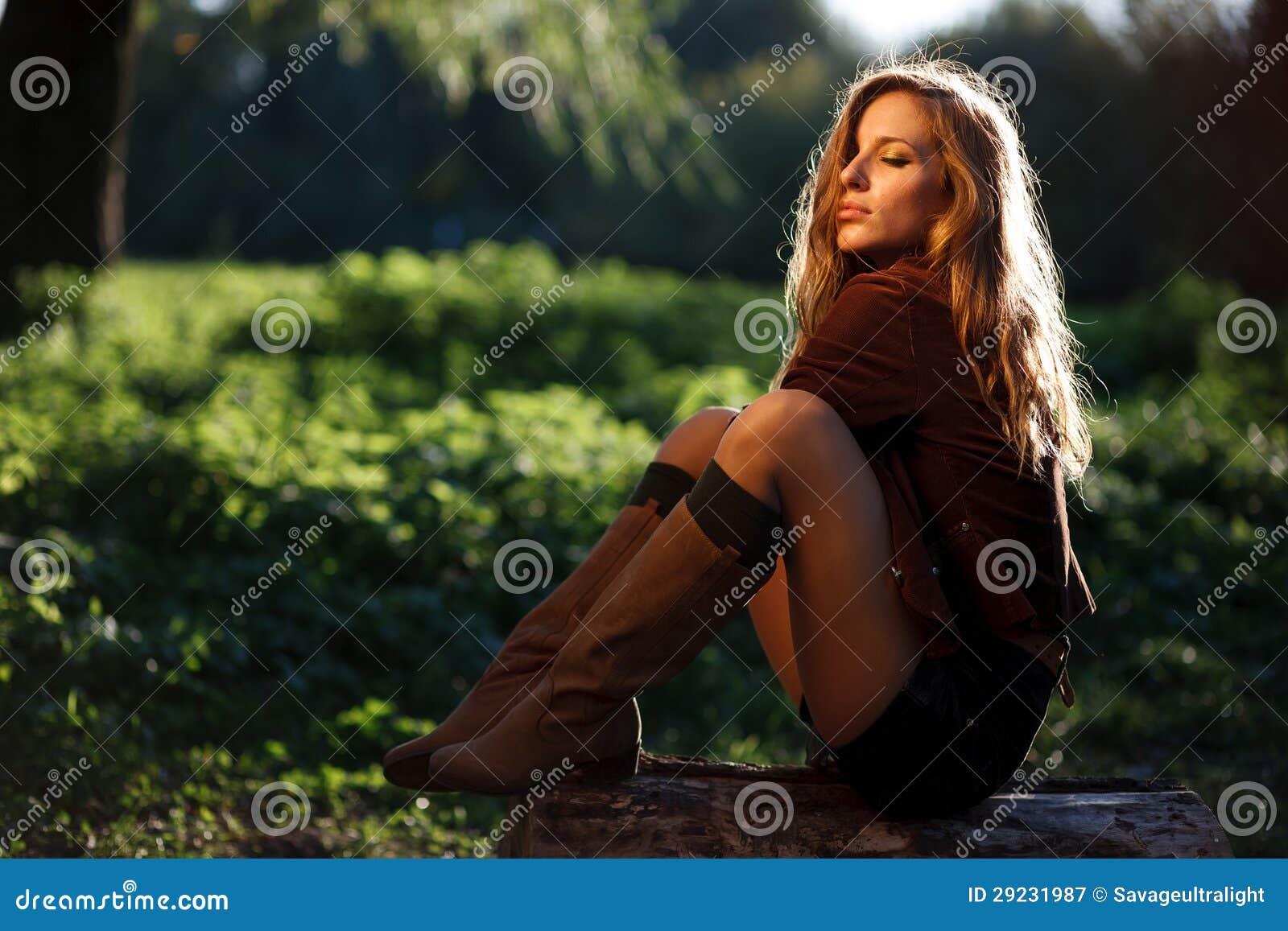 Jeune femme sexy s asseyant sur la pose de log