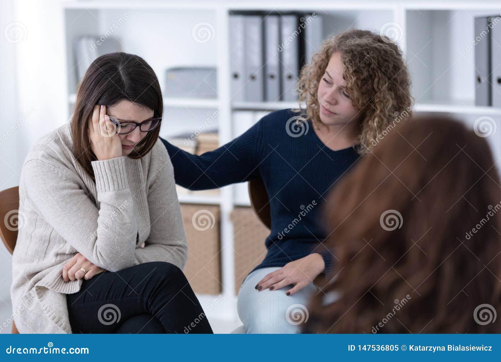 Jeune femme soutenant le patient triste au comité de soutien des questions des femmes