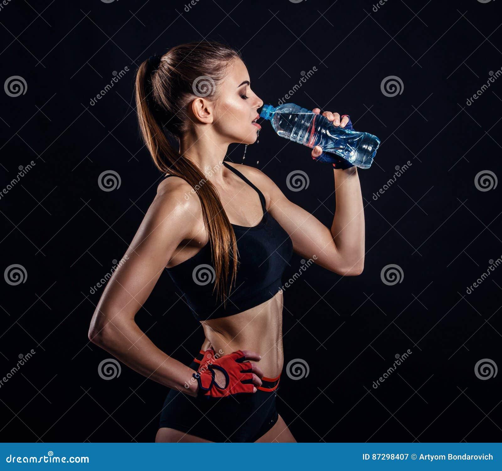 Jeune femme sportive en eau potable de vêtements de sport dans le studio sur le fond noir Chiffre femelle idéal de sports