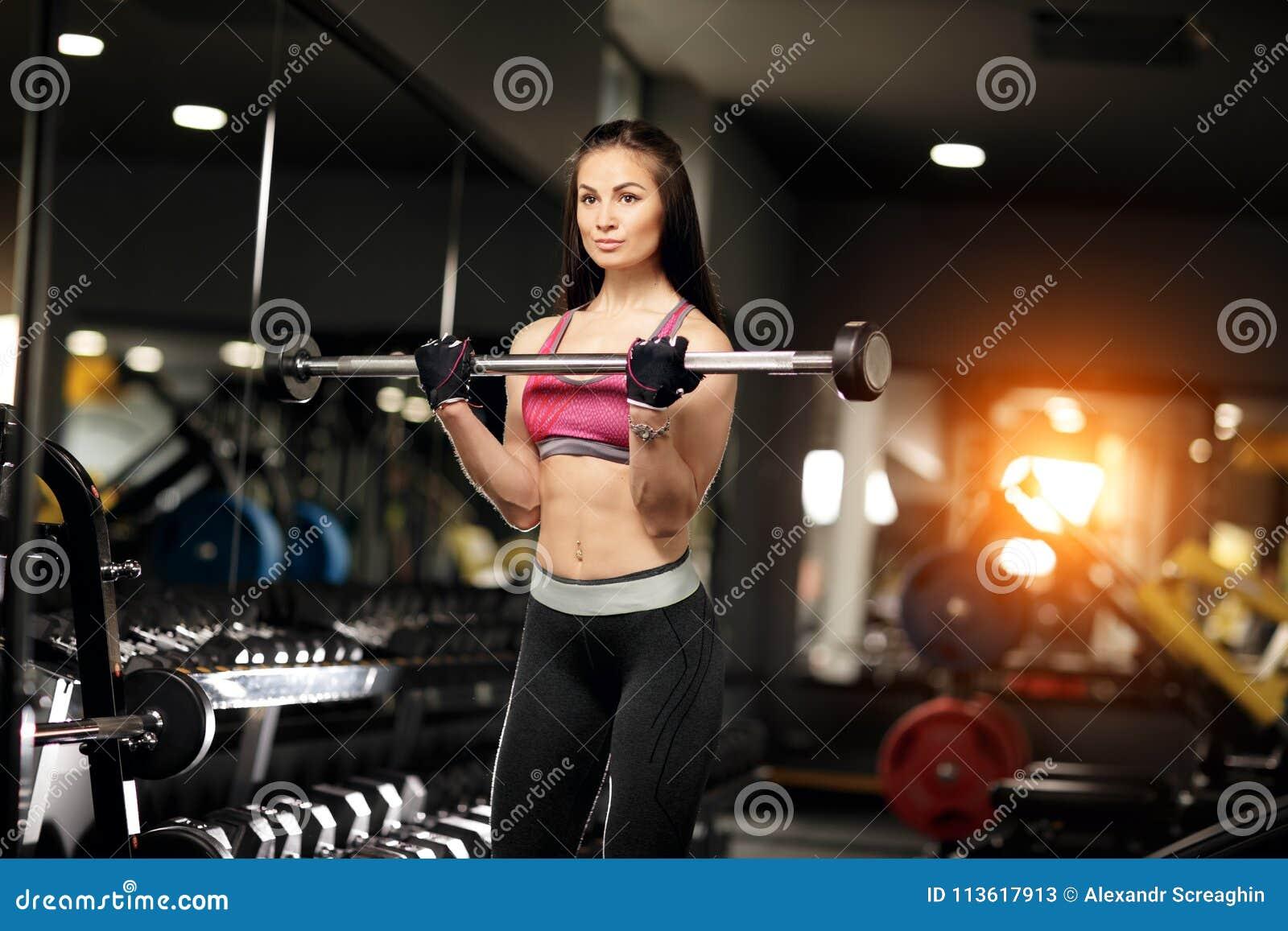 Jeune femme sportive faisant l exercice lourd d haltère pour le biceps dans  le gymnase ab8d1cb8408