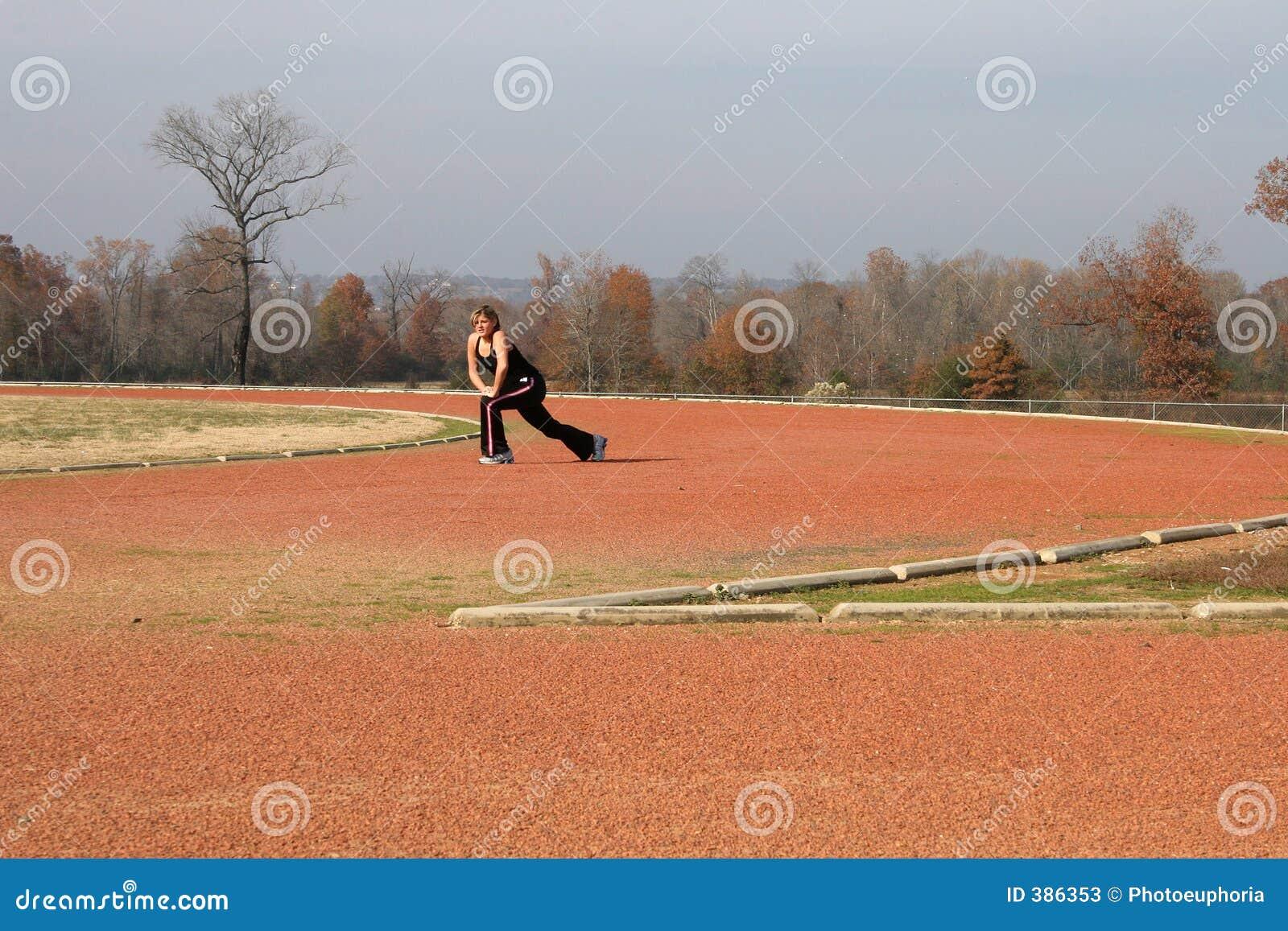 Jeune femme sportive s étirant à la piste