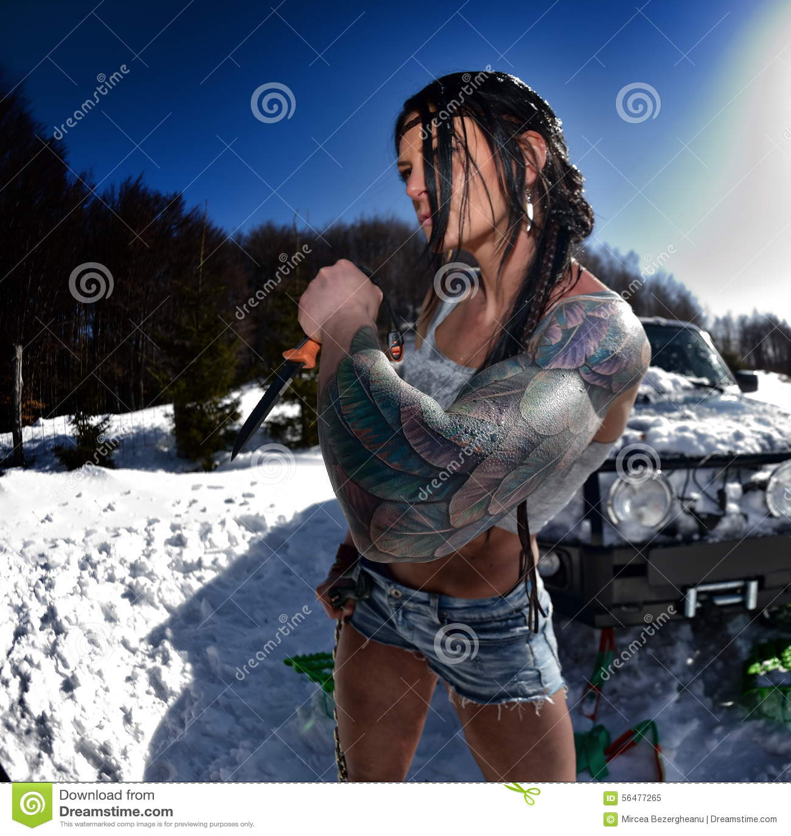 Jeune femme sportive tirant la voiture en hiver