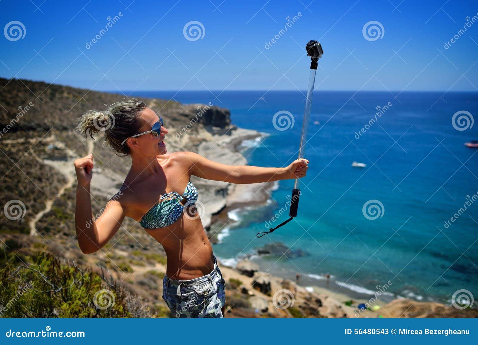 Jeune femme sur la plage en été utilisant le gopro