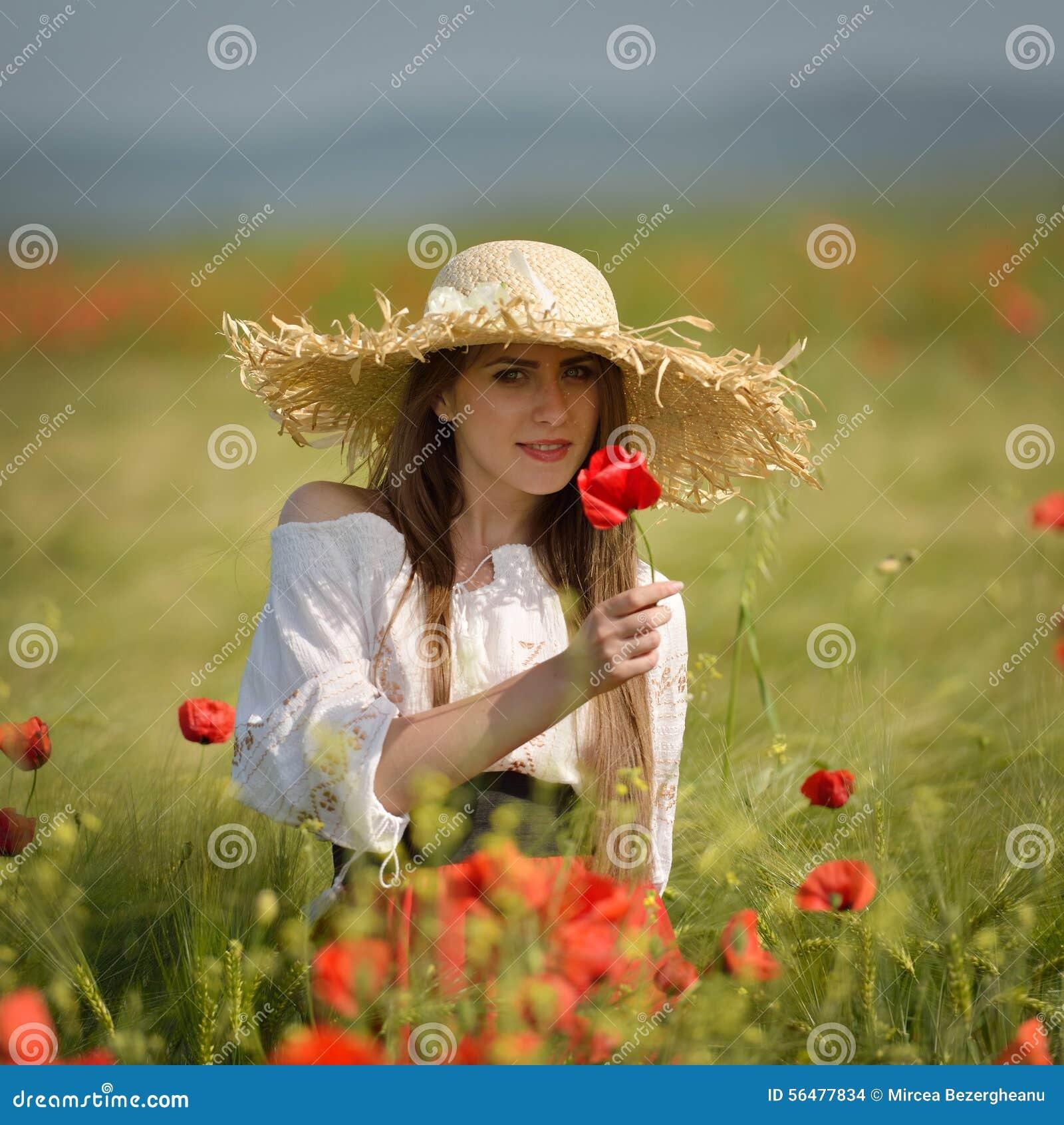 Jeune femme sur le gisement de céréale avec des pavots en été
