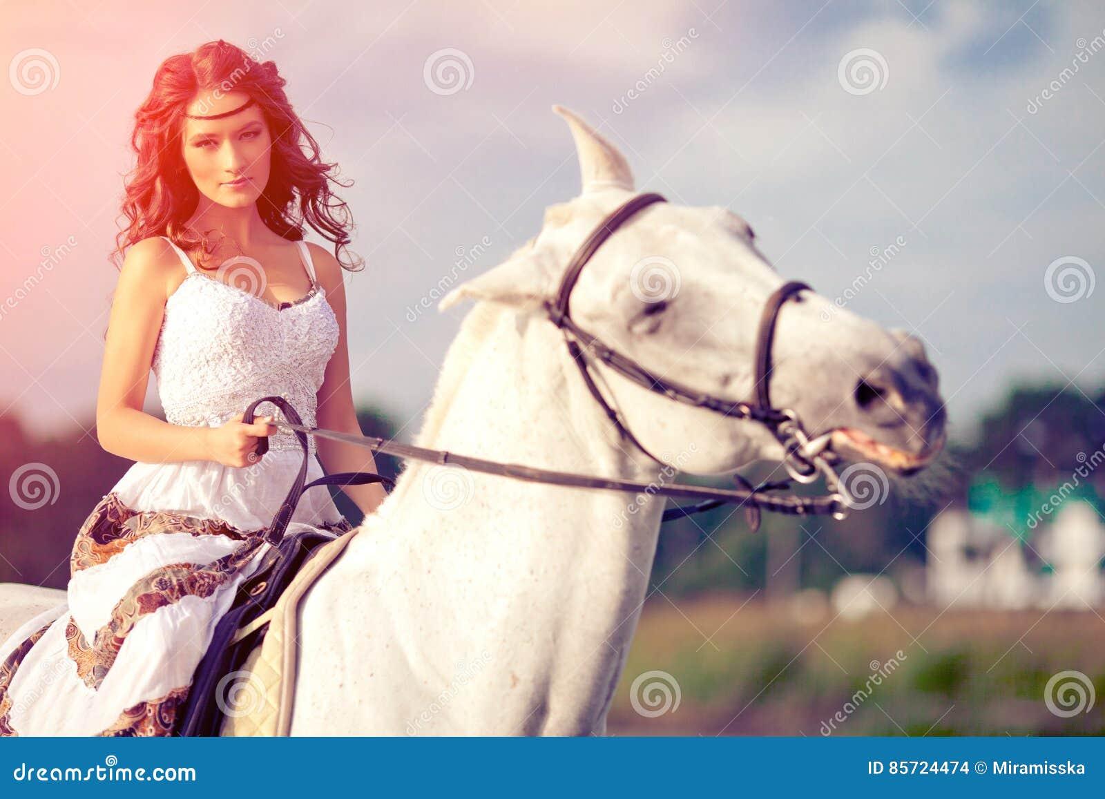 Jeune femme sur un cheval Cavalier de horseback, cheval d équitation de femme sur b