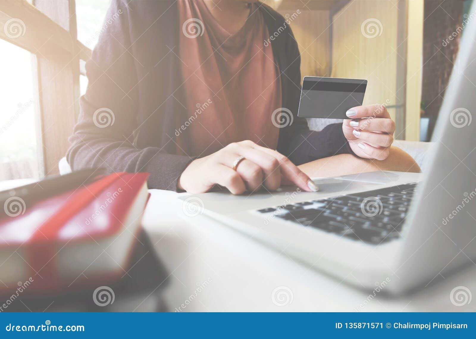 Jeune femme tenant la carte de crédit et à l aide de l ordinateur portable Concept en ligne d achats