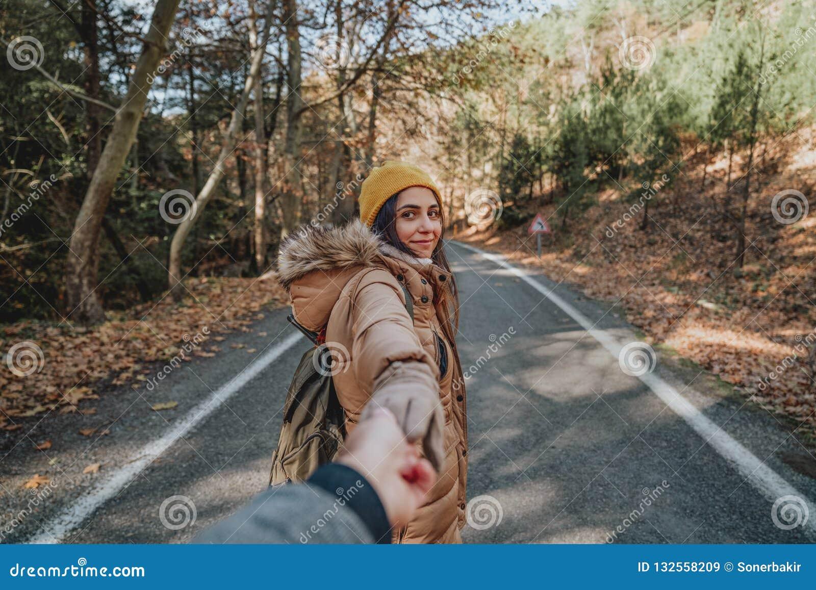 Jeune femme tenant la main du ` s d homme et le menant sur la nature Couples dans l amour
