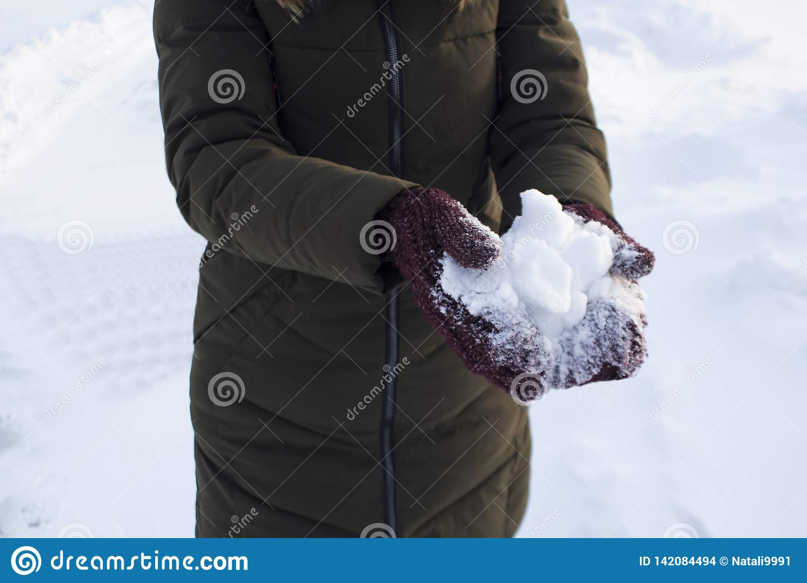 Jeune femme tenant la neige dans des ses mains dans des mitaines, hiver, amusement, joie, sports, récréation, enfants