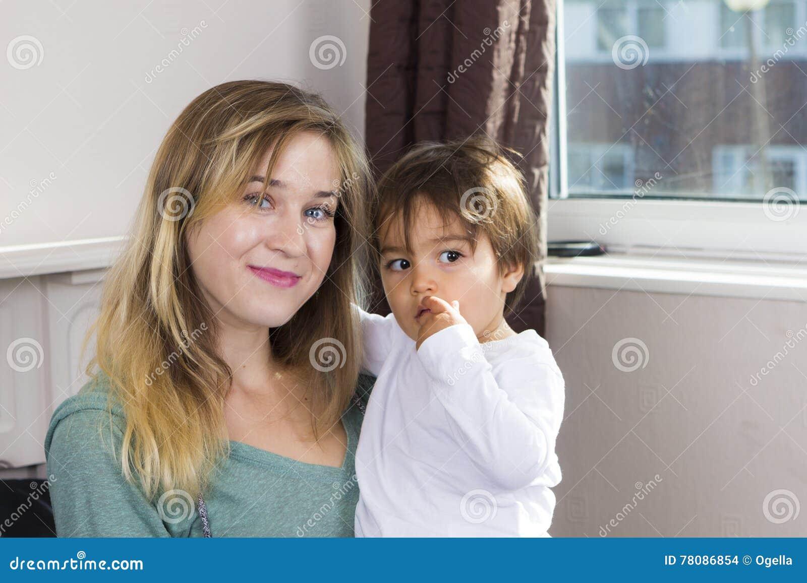 Jeune femme tenant le fils sur des bras