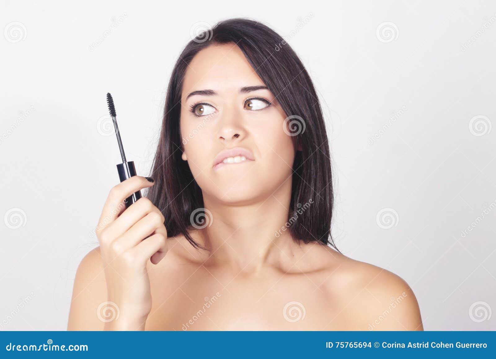 Jeune femme tenant le mascara pour ses cils