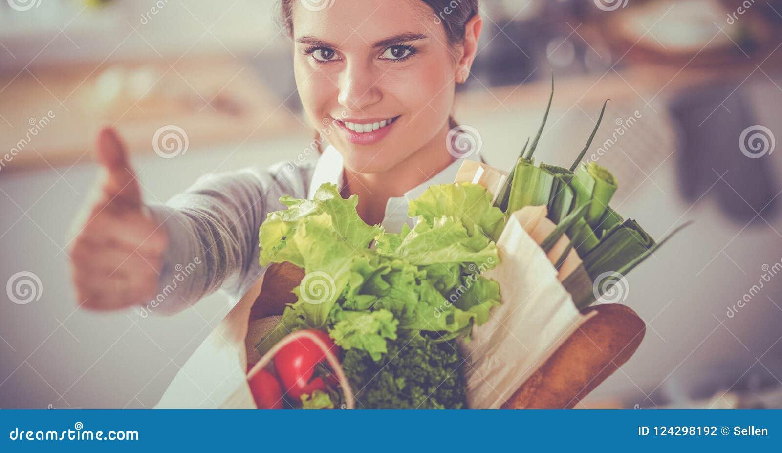 Jeune femme tenant le sac d épicerie avec des légumes et montrant correct