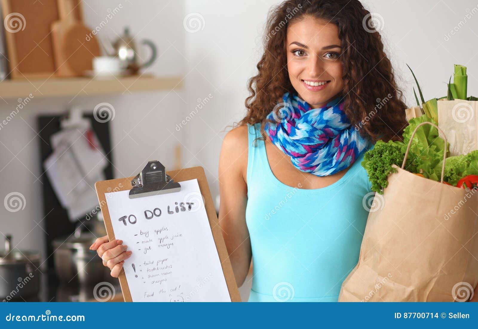 Jeune femme tenant le sac d épicerie avec des légumes se tenant dans la cuisine