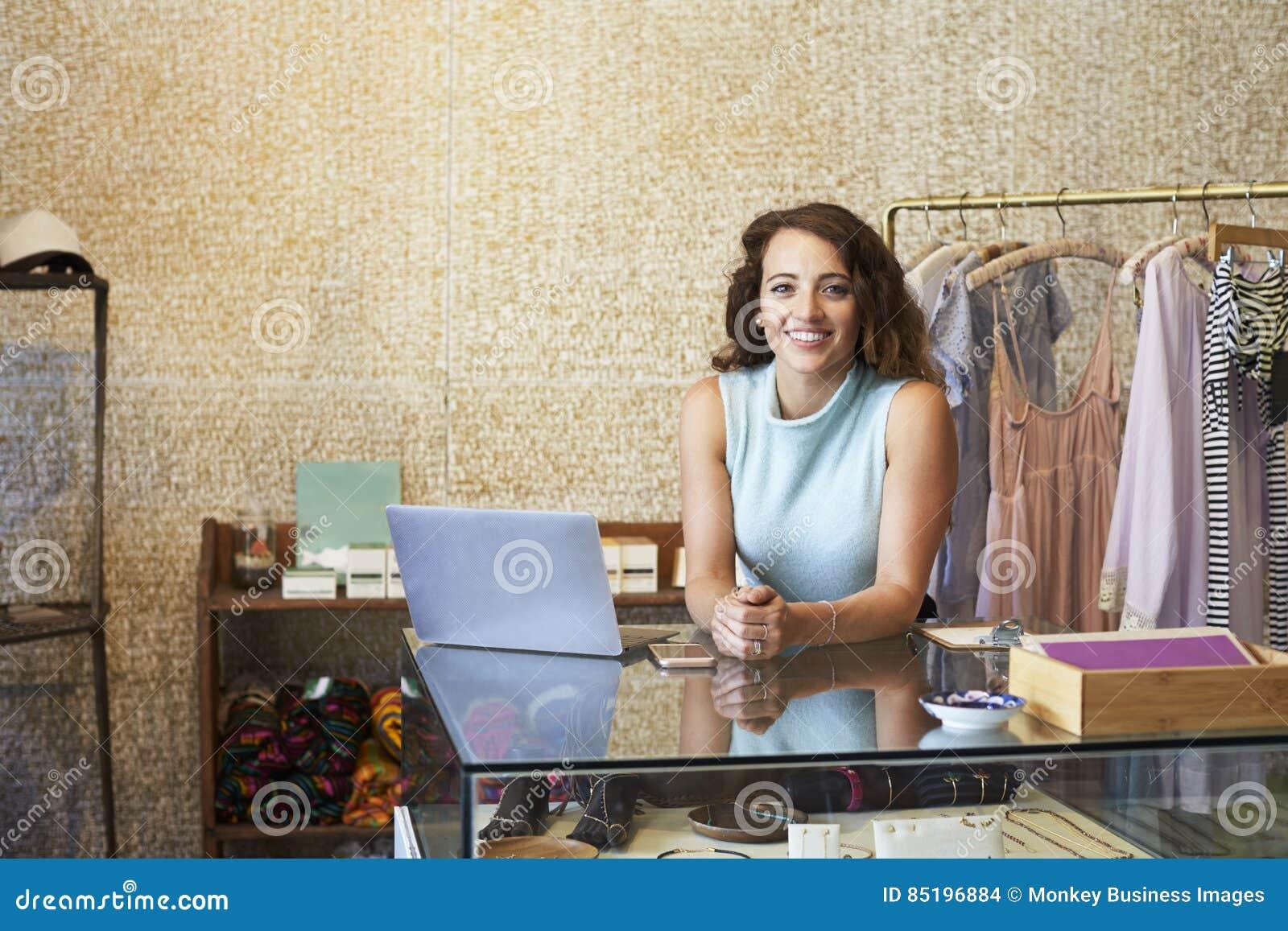 Jeune femme travaillant dans la boutique de vêtements se penchant sur le compteur
