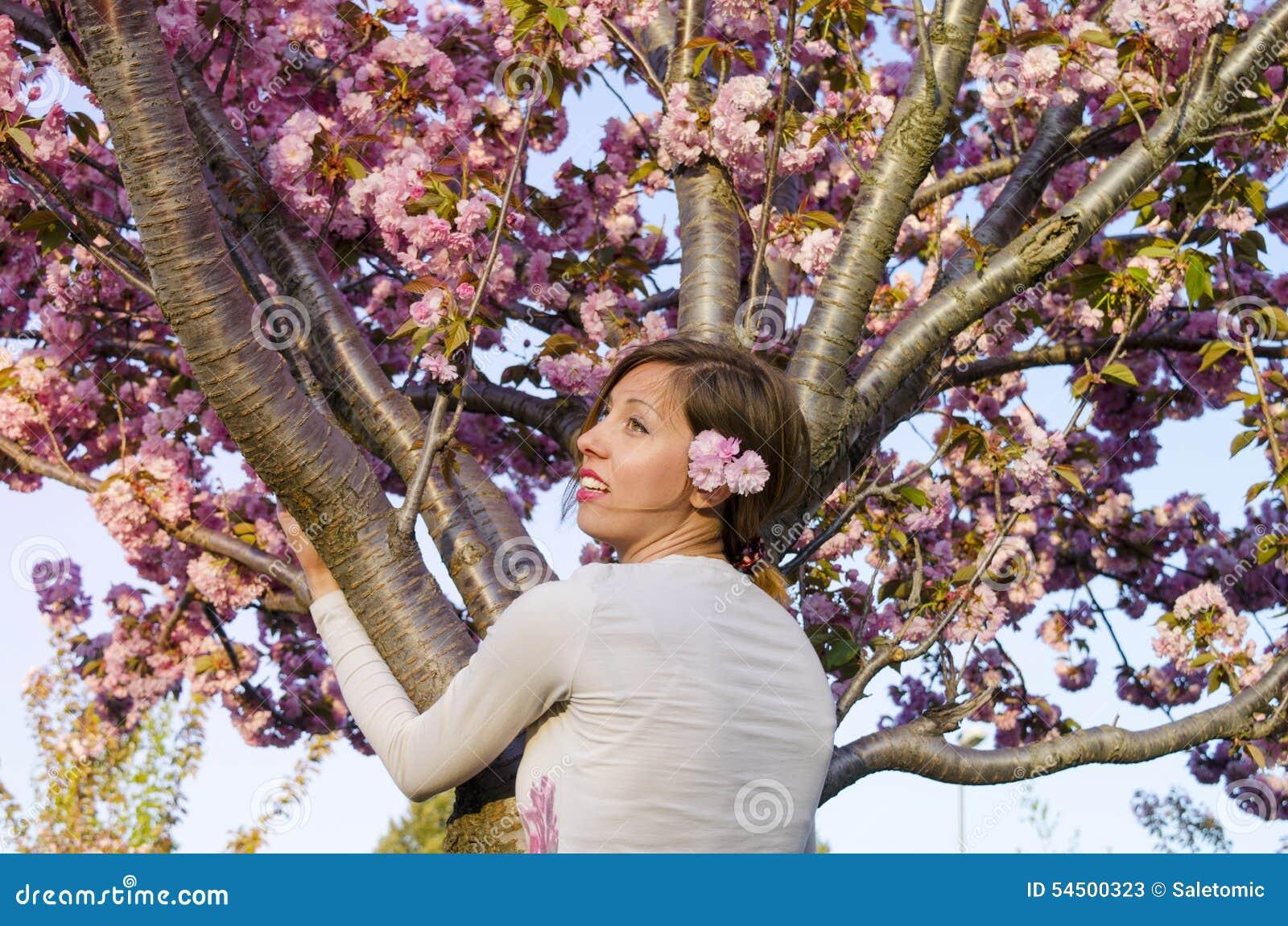Jeune fille étreignant l arbre dans la fleur