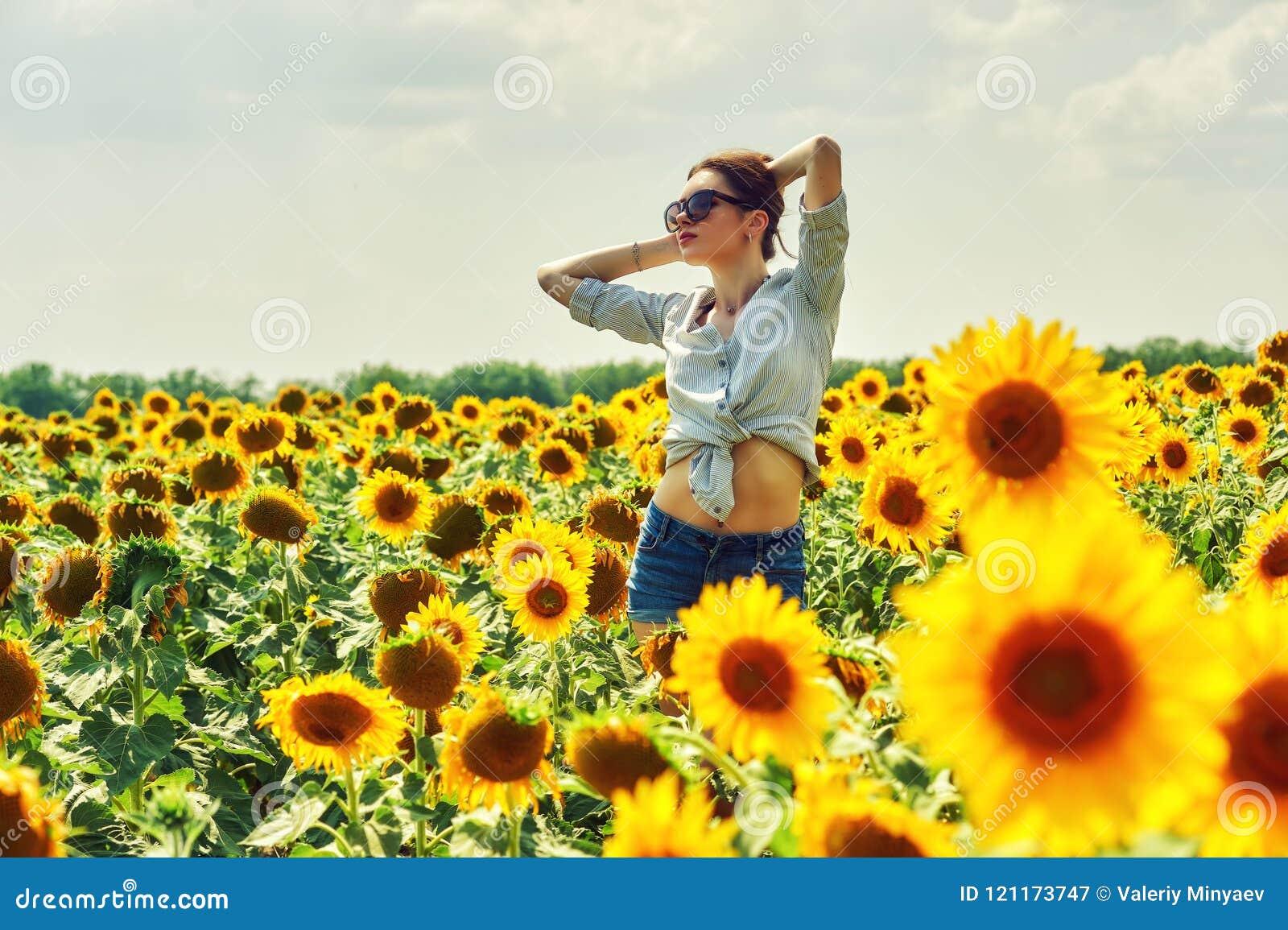 Jeune fille attirante dans le domaine avec des tournesols