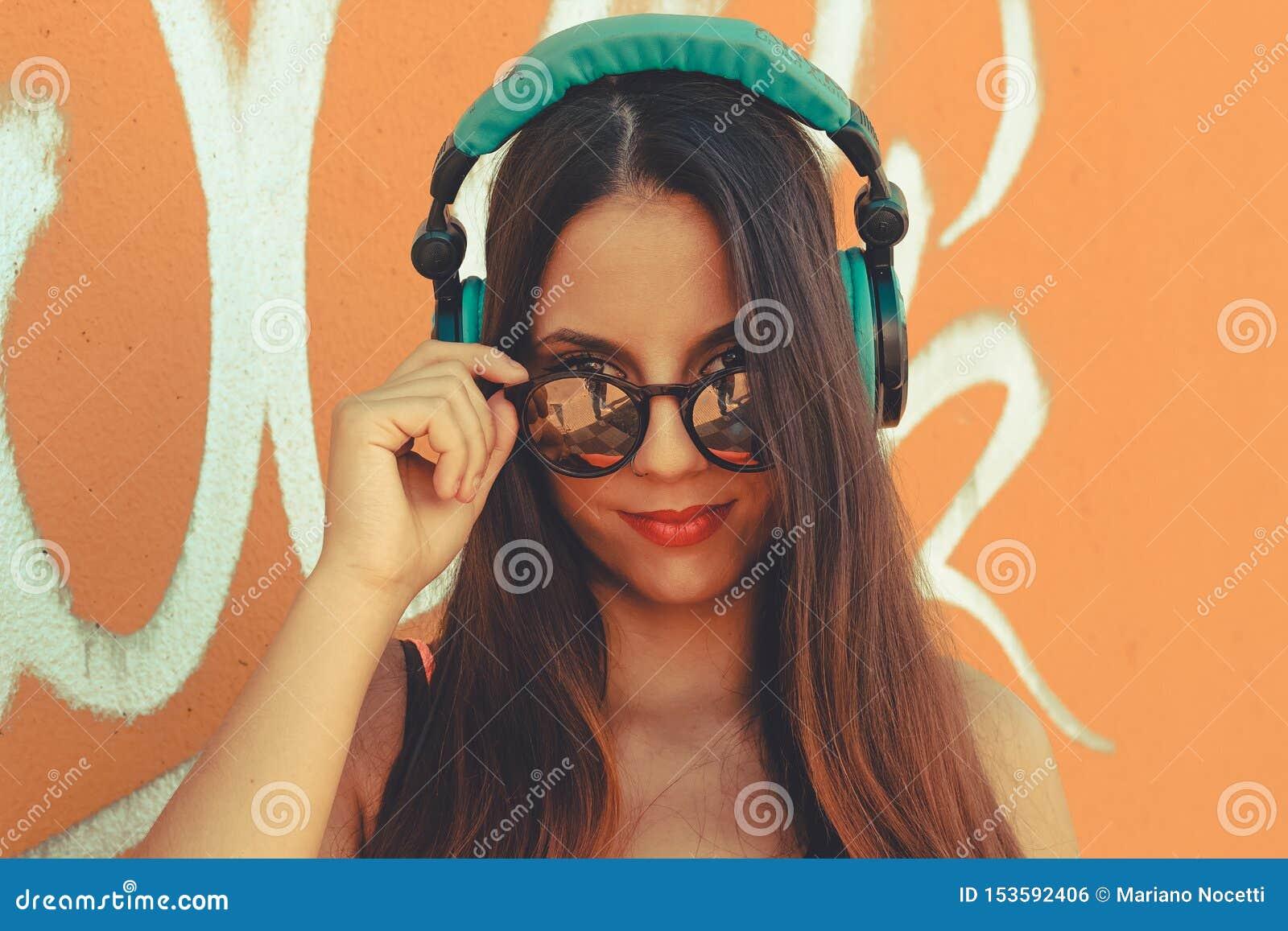 Jeune fille attirante regardant la caméra tandis qu écoutent la musique