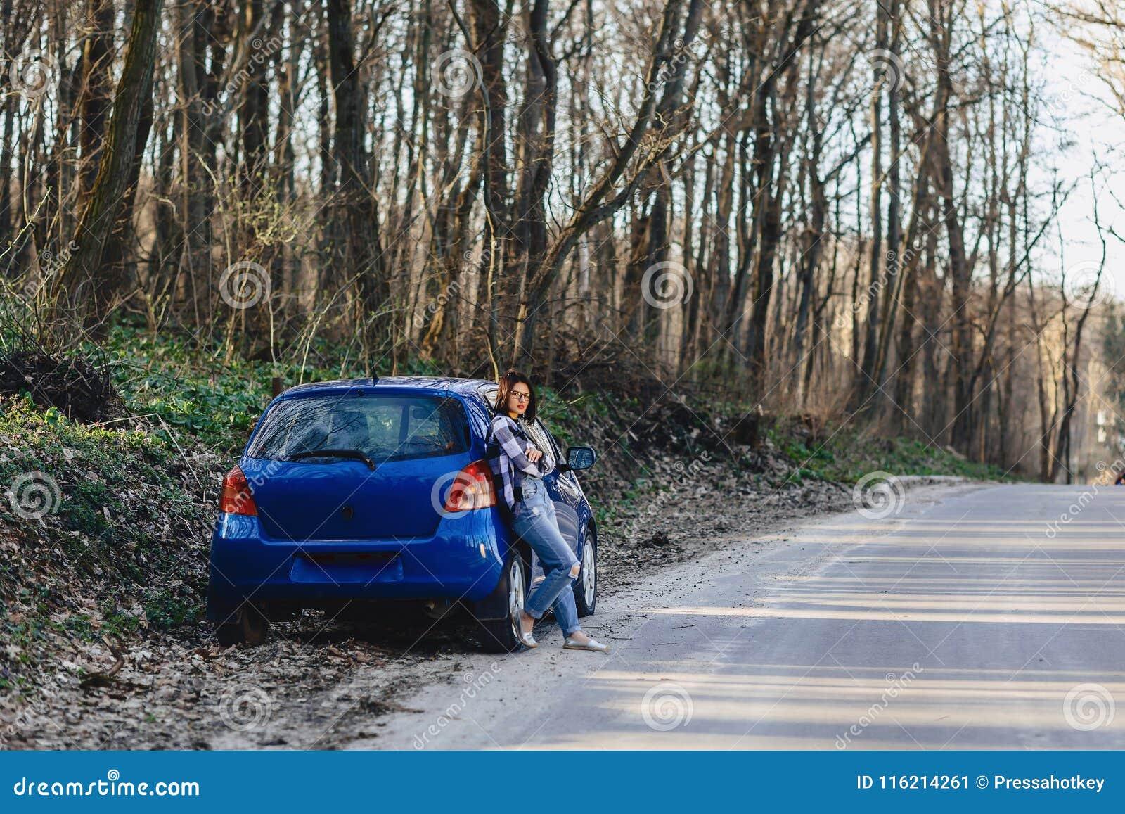 Jeune fille attirante sur la route près de la voiture