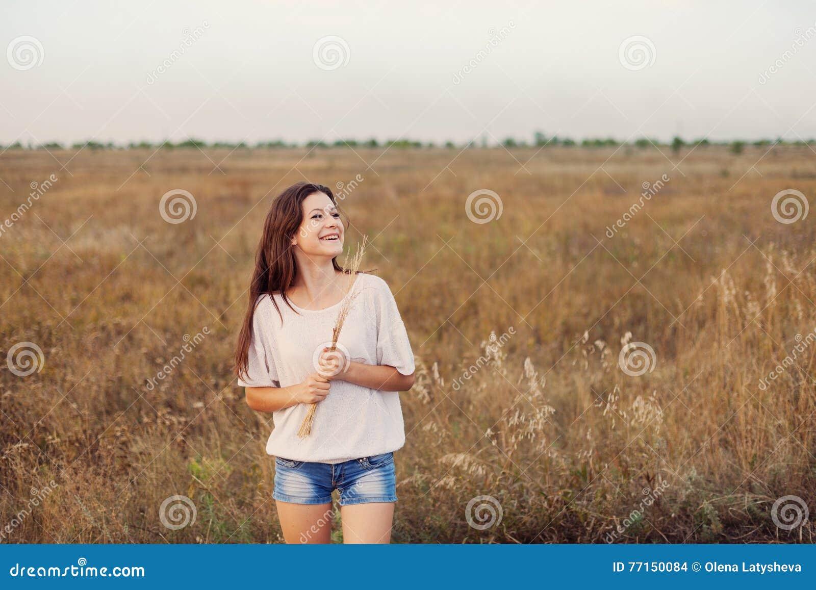 Jeune fille avec de longs cheveux bruns se tenant au pré d automne