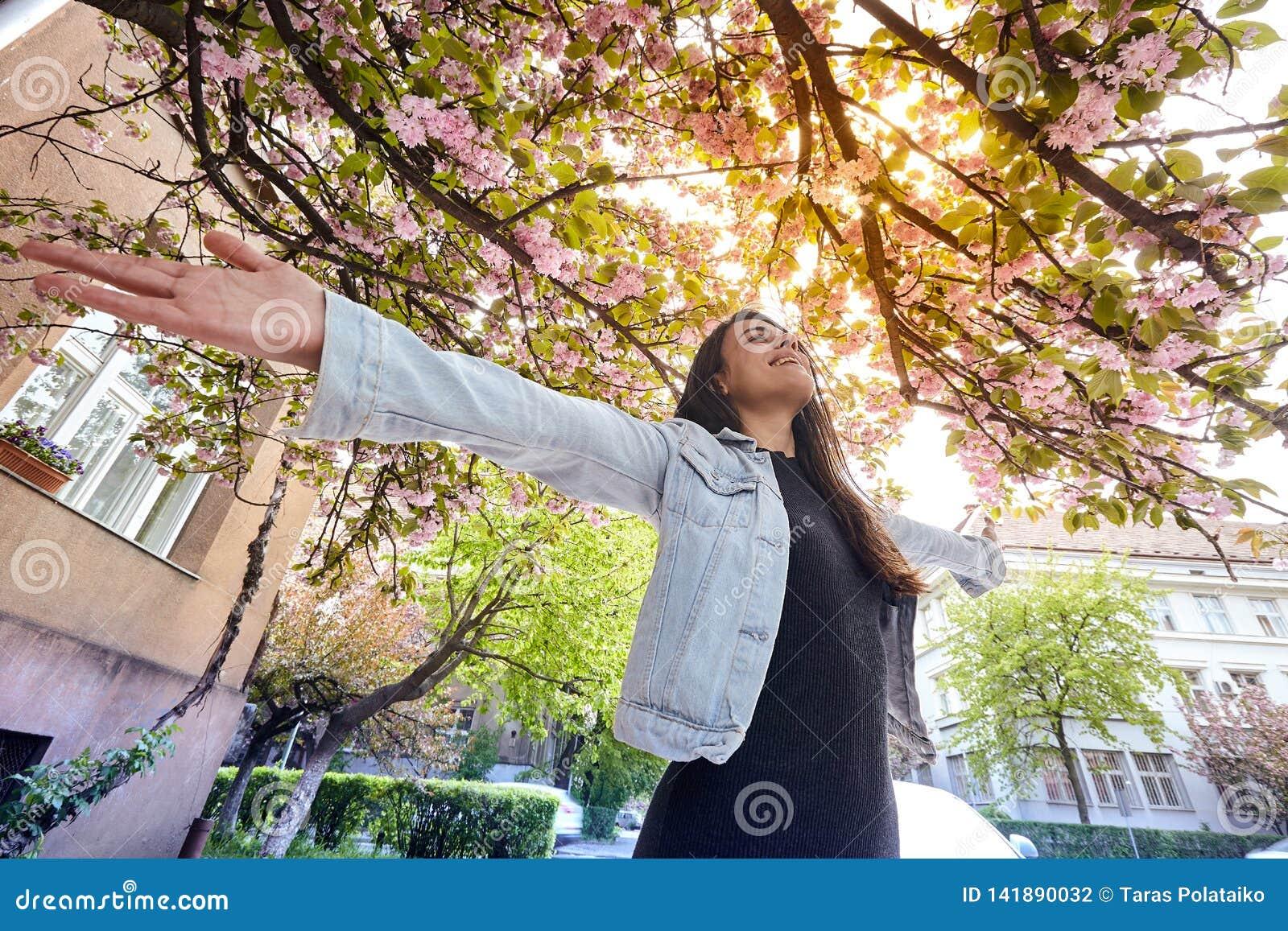 Jeune fille avec des bras grands ouverts et enjoing la rue de cerisier