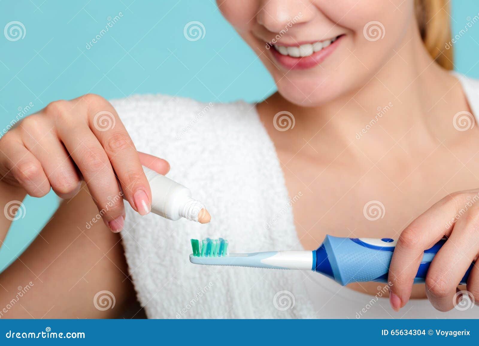 Jeune fille avec la pâte dentifrice et la brosse à dents